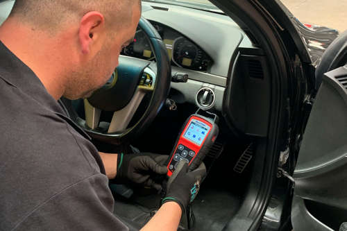 Technician using Autel TPMS tool to diagnose car